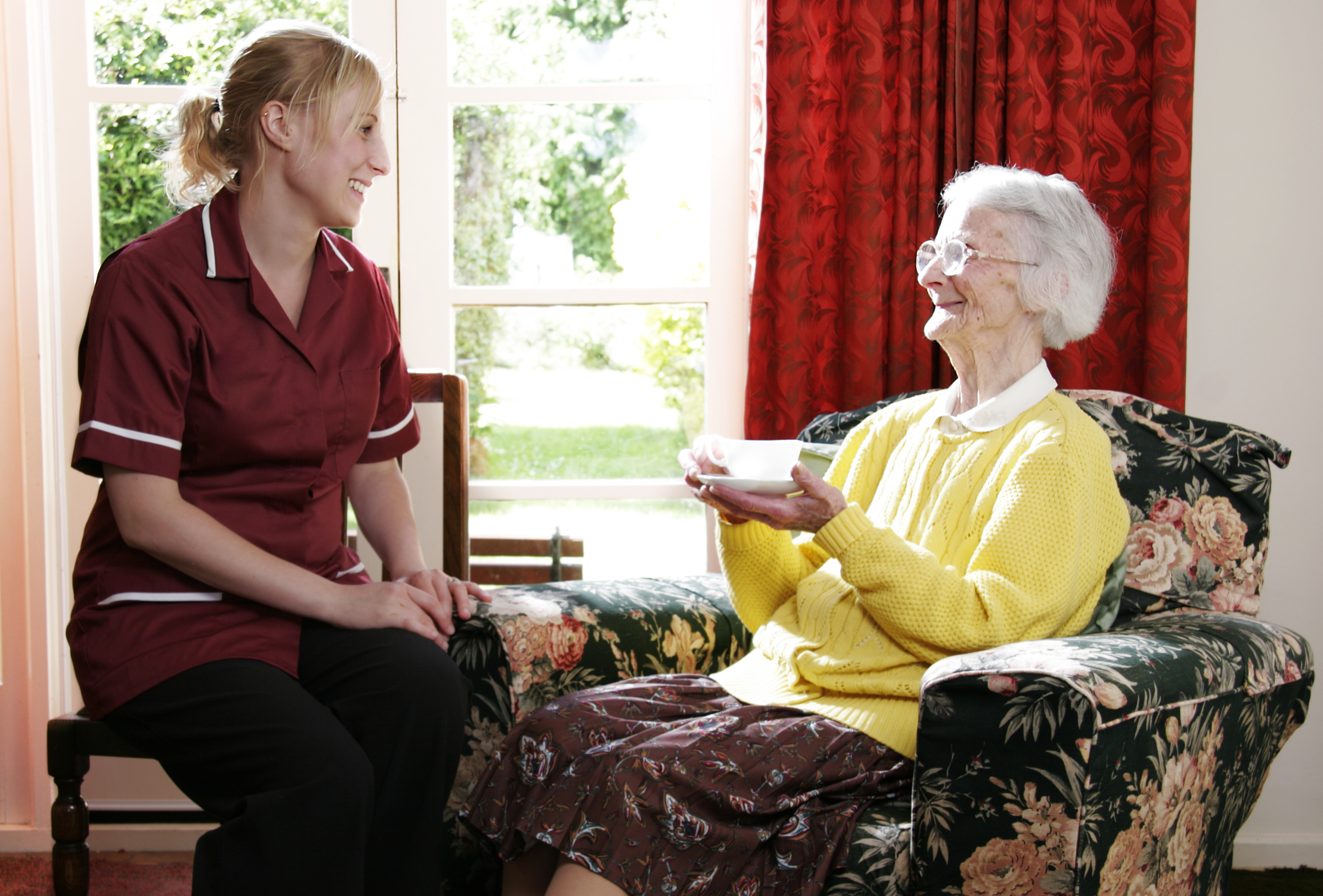 A young pregnant carer enjoys a cup of tea and a chat with her elderly home care pacient